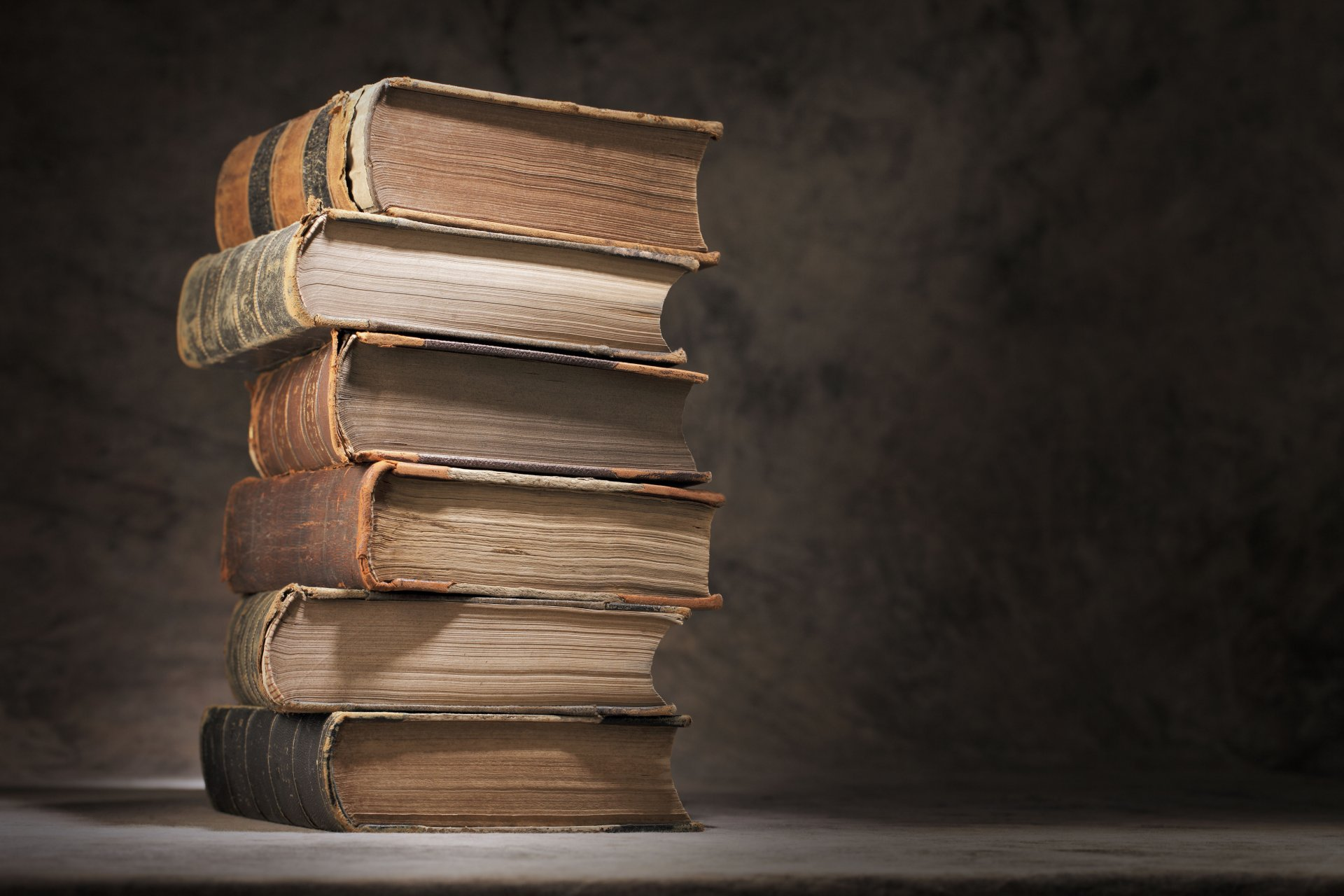 books knowledge table stack vintage luxury folios teaching light and ignorance is darkness blur bokeh close up grey background wallpaper.